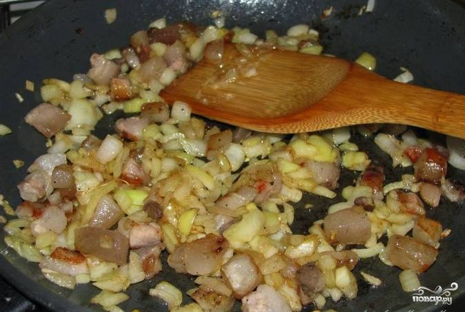 Мясо нарежьте некрупными кусочками. Лук очистите от кожуры и мелко нарежьте. Нагрейте сковороду и выложите туда мясо с луком. Масло добавлять не нужно, мясо даст жир. Обжарьте всё до золотистой корочки.