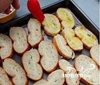 С батона срезать корочку, а мякиш нарезать кубиками или ломтиками. Уложить на противень, сбрызнуть оливковым маслом. Запекать в духовке 7-10 минут - до золотистого цвета.