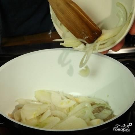 В кастрюле разогреть масло, обжарить некрупно нарезанный лук.