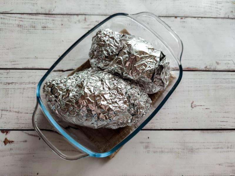 Заверните курицу в фольгу, выложите на противень и отправьте в предварительно разогретую духовку до 180 градусов на 30 минут.