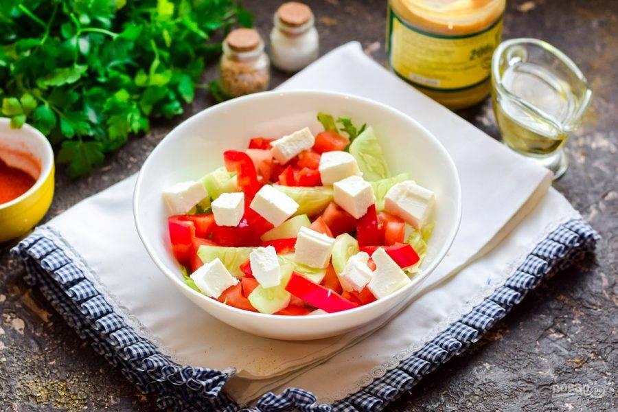 Фету нарежьте кубиками и переложите к овощам.