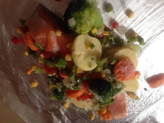 Выкладываем на фольгу лосося, а вокруг распределяем овощи. Посыпаем овощи солью и перцем.