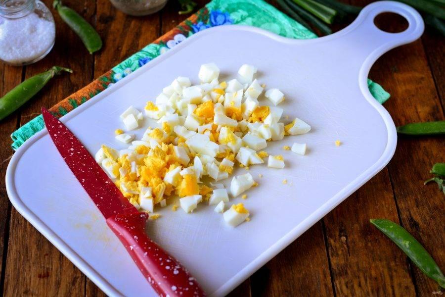 Сварите куриные яйца вкрутую, остудите, почистите и нарежьте кубиками среднего размера.