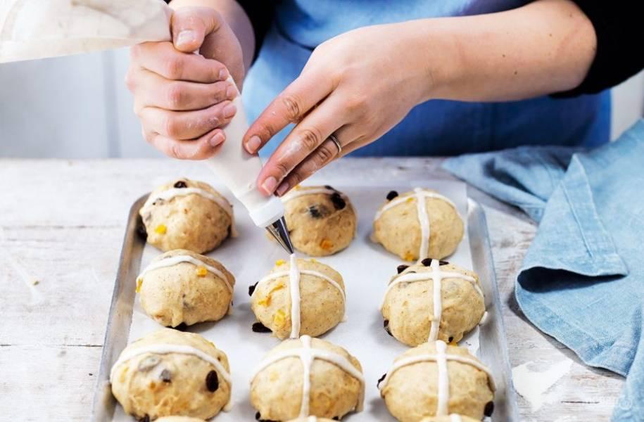 4. В небольшой емкости замесите 100 грамм муки и 6 столовых ложек воды. Поместите смесь в кондитерский мешок, с его помощью нарисуйте на булочках кресты.