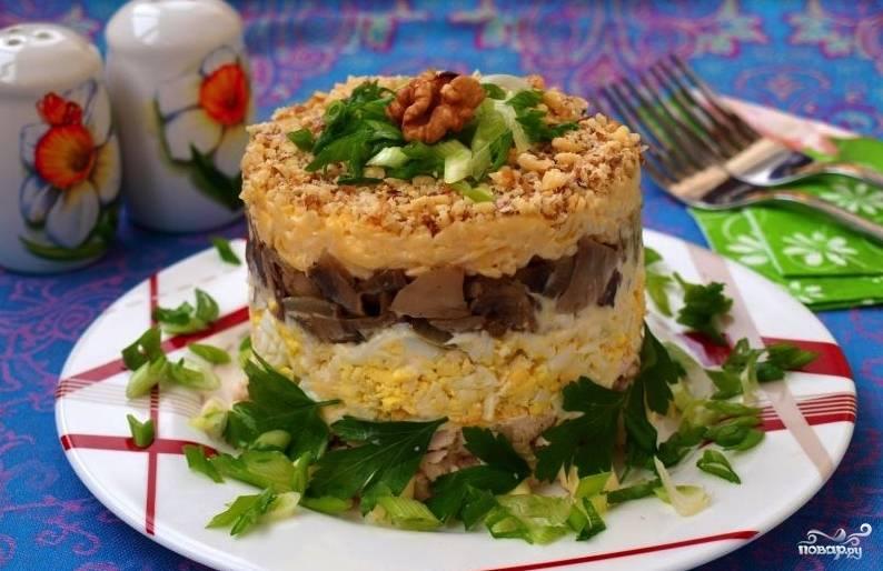 В завершение сверху нужно выложить грецкие орехи. Очистите их и мелко нарубите острым ножом. Выложите наверх салата, слегка прижмите. Аккуратно снимите кольцо — и подавайте салат. Блюдо можно украсить нарубленной зеленью.