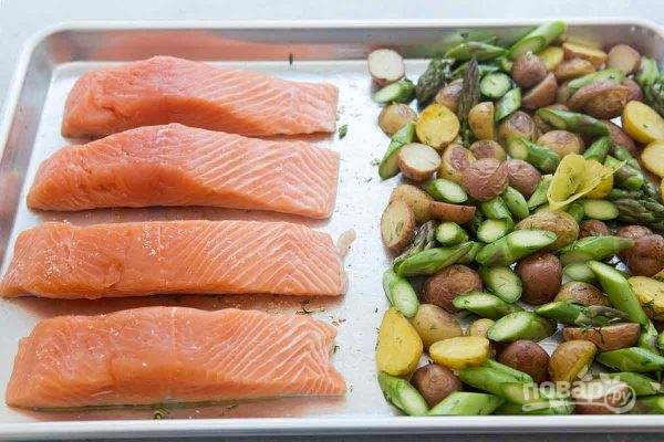 Филе семги нужно немного посолить, а затем положить на противень вместе с овощами. Оставляем противень с семгой и картошкой еще на 10-12 минут в духовке.