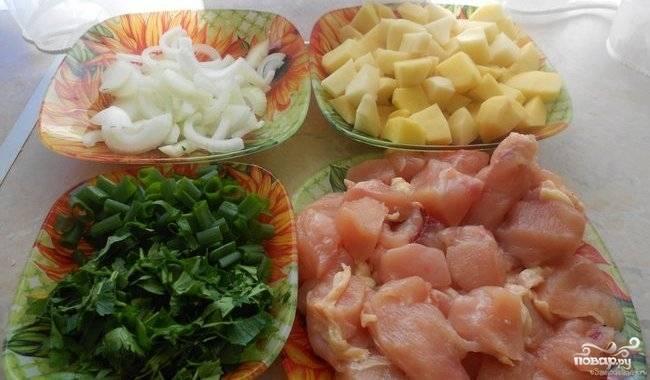 Картофель почистите, помойте и нарежьте кубиками. Грудку промойте и нарубите порционными кусками. Лук почистите, нашинкуйте полукольцами. Зелень и зелёный лук помойте и измельчите.
