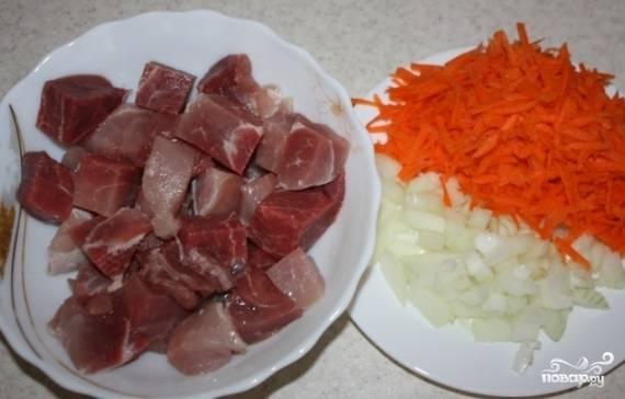 Мясо промойте и нарежьте кусочками 3 на 3 см. Лук почистите и нашинкуйте. Морковь помойте, почистите и натрите на крупной тёрке.