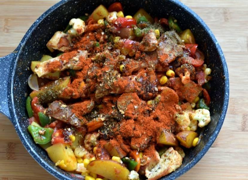 Выложите кукурузу, посыпьте паприкой и пряностями, посолите и поперчите по вкусу. Перемешайте, накройте крышкой и отключите нагрев.