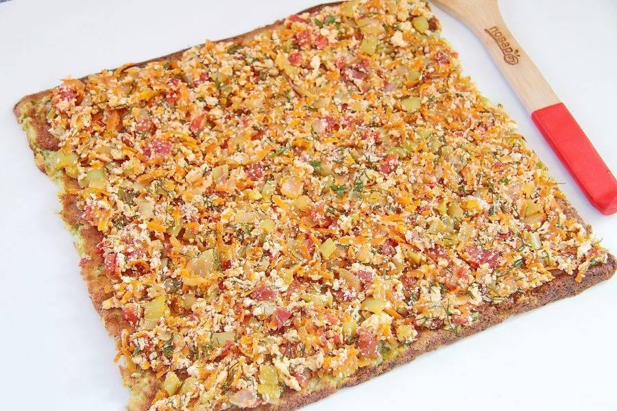 Переверните остывшее тесто бумагой вверх и аккуратно ее снимите. Выложите сверху равномерно овощную начинку.