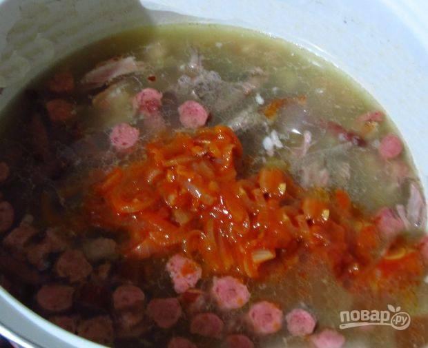 В кастрюлю выложите  вареное мясо, всю колбасу, огурчики, зажарку и влейте бульон. Хорошо перемешайте, готовьте 15 минут.