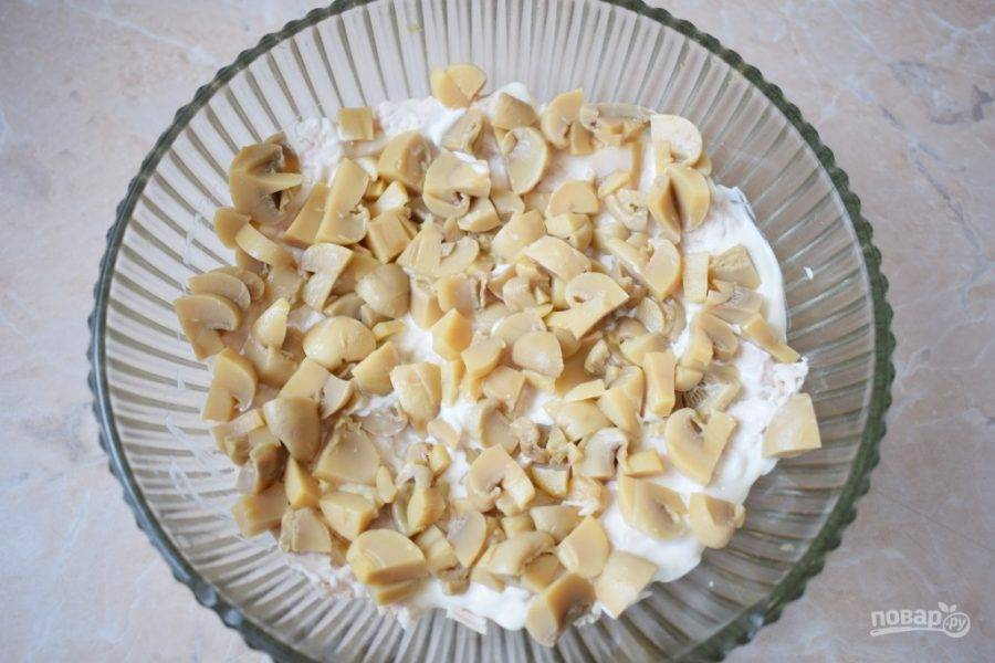 Из консервированных шампиньонов слейте жидкость, а сами грибы мелко нарежьте и выложите в салат следующим слоем. Добавьте немного майонеза.