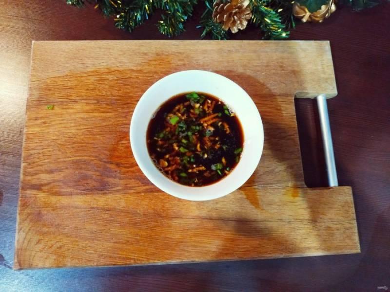Пока готовятся наши пельмени, можно сделать подходящий китайский соус. Для этого порежьте вторую часть зеленого лука, раздавите зубчик чеснока и немного имбиря, залейте уксусом и соевым соусом в равных частях. Соус готов.