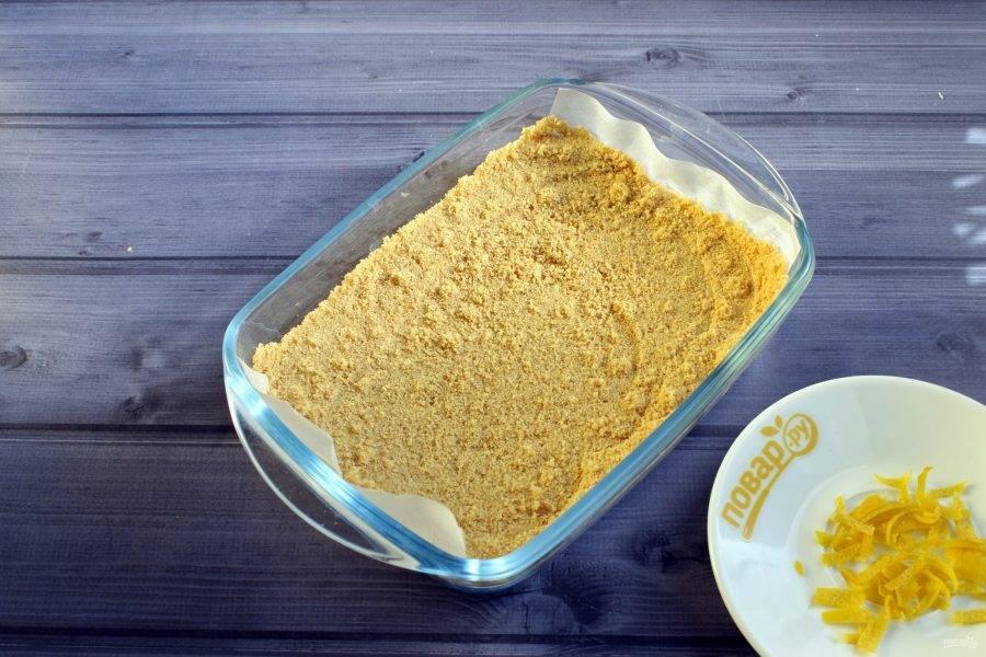 Печенье измельчите в крошку. На дно формы  (14х18 см) постелите пергамент для выпечки. Утрамбуйте крошку печенья по дну формы.