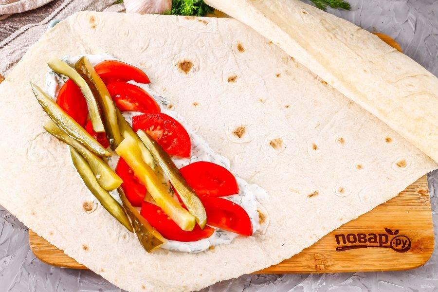 Смажьте половиной соуса край тонкого армянского лаваша, выложите на него нарезанные помидоры и огурец.
