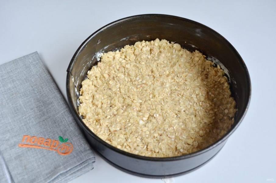 7. Форму для выпечки (диаметр 20 или 22, не больше) застелите пергаментом, смажьте маслом. Положите две трети овсяной крошки, хорошо утрамбуйте ложкой или вилочкой, как удобно.