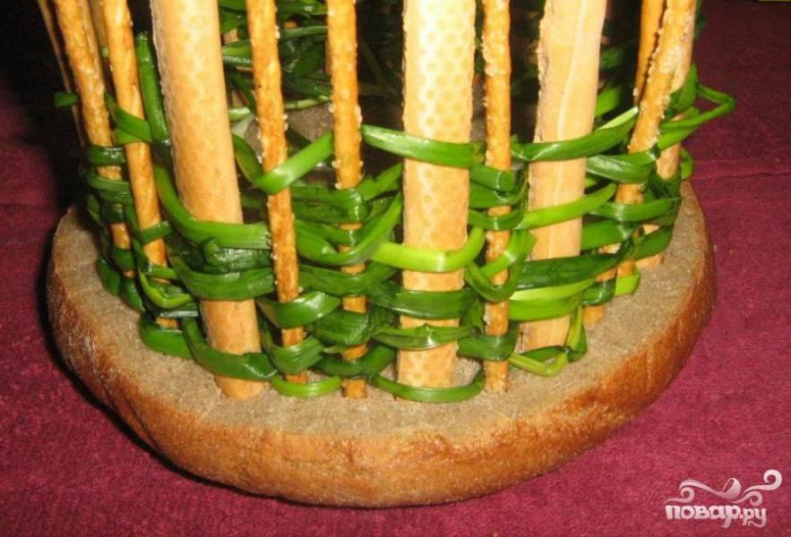 Вымачиваем зеленый лук в холодной воде (можно оставить его в холодильнике на 1 час). Затем плетем стены, пропуская перья лука между частоколом. Концы лука заправляем внутрь.