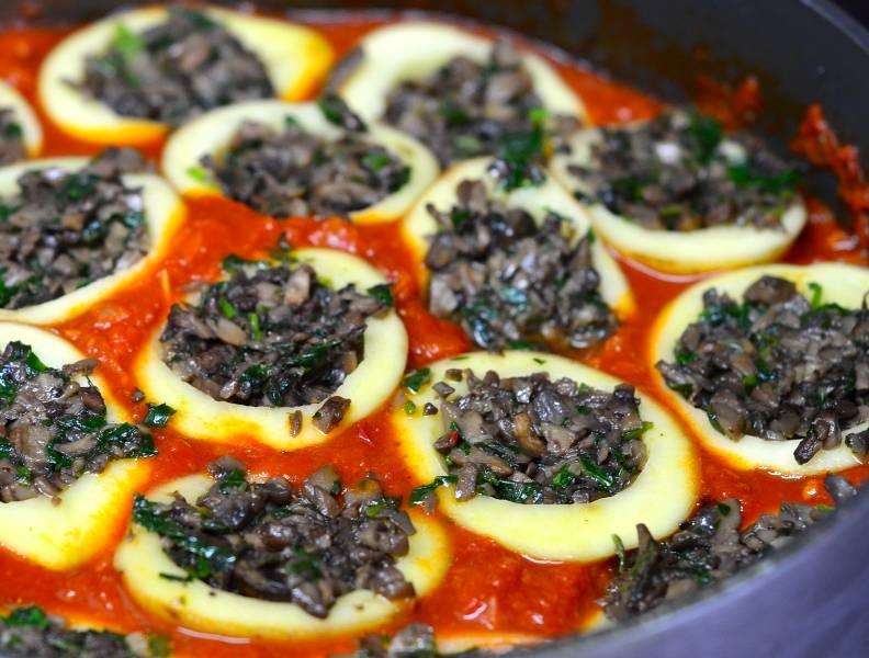 В сотейник, где жарили грибы, добавляем еще ложечку масла и выкладываем в сотейник измельченный лук-шалот, а также оставшийся измельченный чеснок, жарим все 6-7 минут на среднем огне до золотистого цвета. После этого добавляем две ложки томатной пасты и тертую морковь, тушим все, помешивая, 6-7 минут. Затем выкладываем в сотейник измельченные помидоры (без кожицы), через 3 минуты добавляем паприку, корицу тмин и соль по вкусу, держим соус на огне еще 5-7 минут. Когда он будет готов, выкладываем в соус нафаршированный картофель начинкой кверху, желательно, чтобы картофель не утопал в соусе.