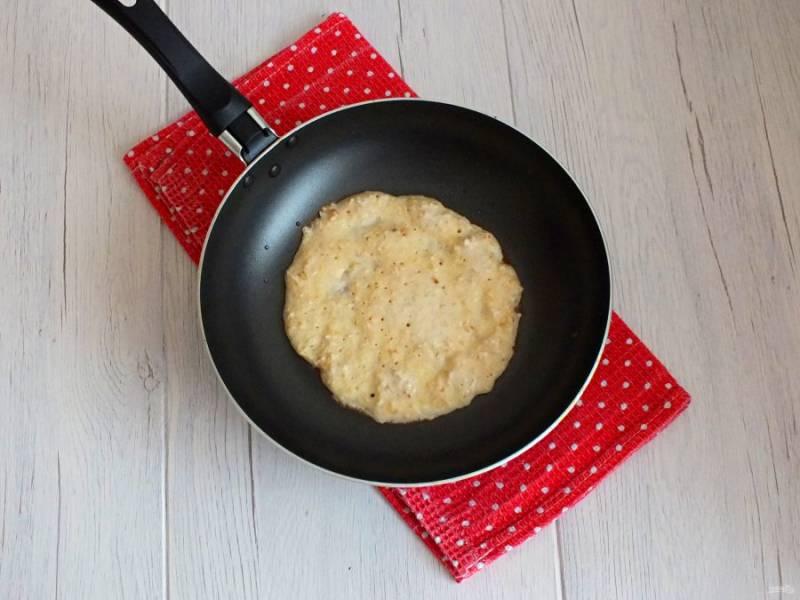 Если необходимо, то смажьте сковороду растительным маслом. Вылейте 1/2 половника, распределите тесто по дну сковороды. Растекаться оно будет трудно, поэтому удобнее это сделать ложкой или половником. Обжаривайте до появления мелких пузырьков на верхней стороне блинчика.