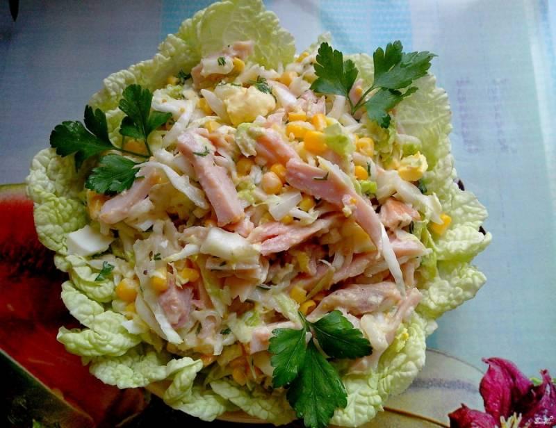 Теперь берем тарелочку и оформляем салат. Кладем вниз листья пекинской капусты. Сверху помещаем на них несколько ложек салата. Украшаем петрушкой или любой другой зеленью. Блюдо готово!
