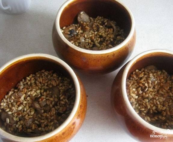 6. В подготовленные горшочки заложите перловку вместе с грибами и луком. Залейте кипящей водой, которая должна прикрывать крупу на пару сантиметров. Горшочки накройте крышкой. Поставьте в холодную духовку посредине. Включите на 230С. Запекайте кашу 20 минут. Затем установите режим прогрева на 180С и готовьте перловку на протяжении часа.