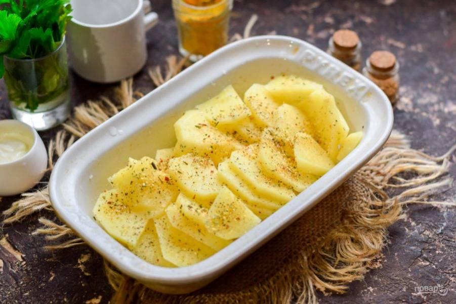 Переложите картофель в форму смазанную маслом. Посыпьте картофель специями по своему вкусу.