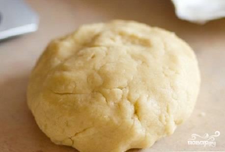 """Сливочное масло натрите на терке. Добавьте 50 гр. сахарного песка, яйцо, ванилин и столовую ложку воды. Затем всыпьте муку. Хорошенько замесите тесто, закрутите его в пленку и оставьте """"отдыхать"""" на 15-20 минут."""