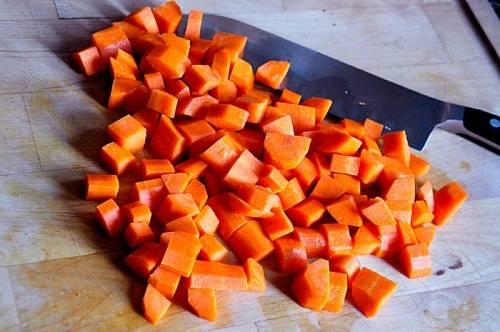 Форма нарезки овощей в жарком не влияет на вкус блюда. Однако, если вся нарезка выполнена кубиками или хотя бы их подобием, готовое блюдо на тарелке будет смотреться лучше. Кроме того, если долго тушить натертую морковь, потом нужно будет постараться, чтобы обнаружить ее в жарком. Поэтому не ленимся, очищаем морковь и нарезаем небольшими кубиками, перекладываем в чистую тарелку.