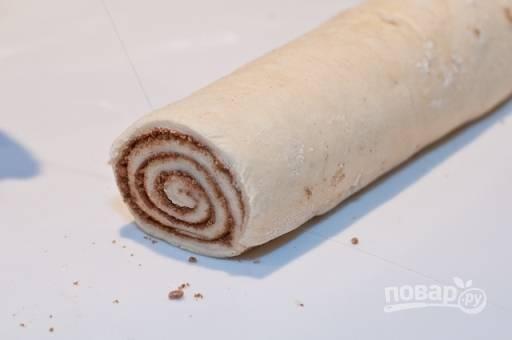 Рулет разрезаем на небольшие булочки очень острым ножом и выкладываем на противень, застеленный пергаментом или смазанный сливочным маслом.