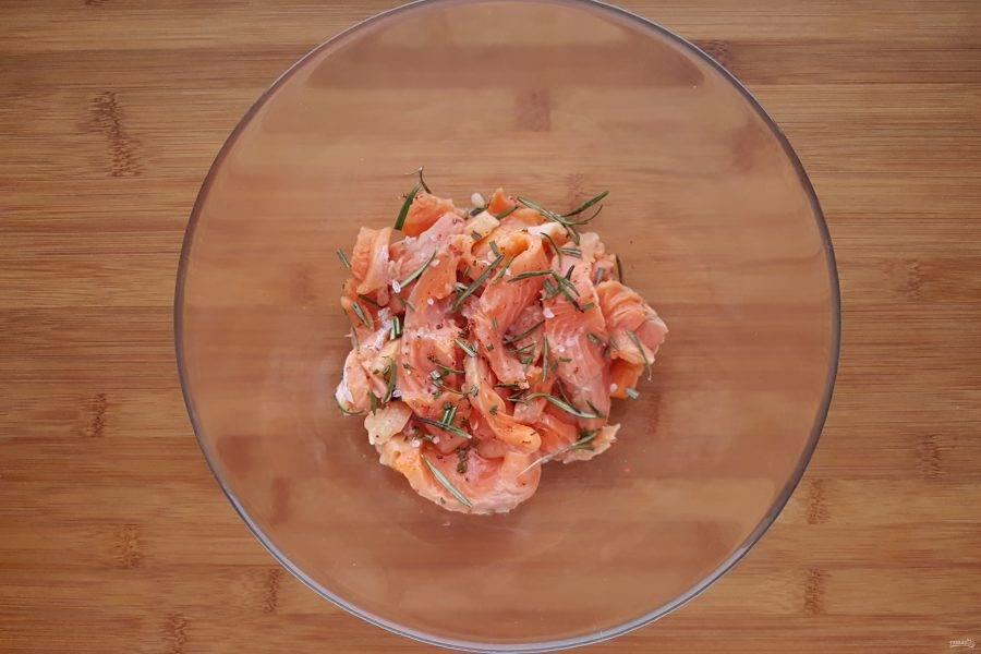 Филе рыбы нарежьте небольшими кусочками, добавьте соль и перец по вкусу, сок половинки лимона и розмарин. Перемешайте, оставьте рыбу мариноваться на 20-30 минут.