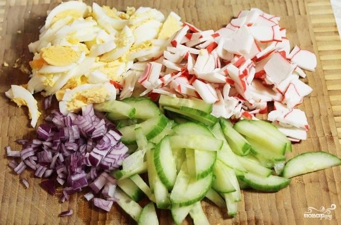 1.Отвариваем яйца, затем нарезаем их соломкой (можно кубиком), лук репчатый, огурец свежий и крабовые палочки нарезаем так же, как и яйца.