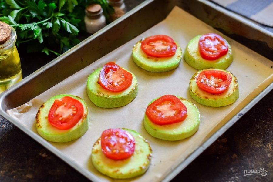 Выложите кабачки на противень, поверх разложите помидоры. Посыпьте кабачки солью и перцем по вкусу.