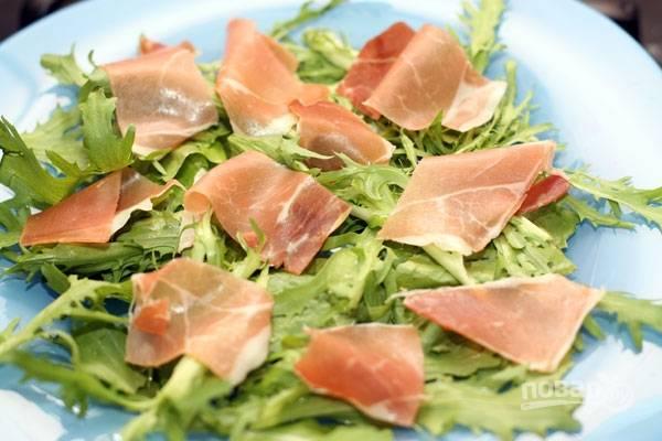 3.Зелень рву руками крупными кусочками и выкладываю на широкое блюдо, затем нарезаю тонко ветчину и раскладываю пласты поверх зелени.