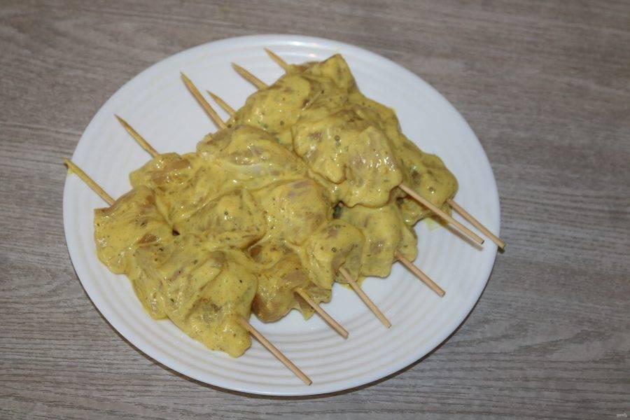 Замаринованную курицу нанизайте на шпажки. Шпажки обязательно смочите водой, чтобы они не горели при выпечке.
