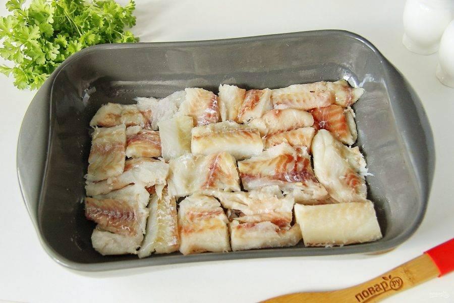 Филе минтая промойте, промокните бумажным полотенцем и нарежьте порционными кусочками. Сложите подготовленное филе в смазанную маслом форму для запекания и полейте лимонным соком.