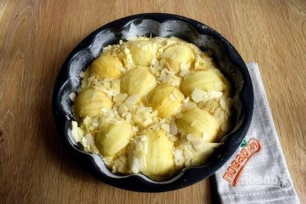 6.     Форму (d – 26см) смажьте маслом, присыпьте мукой. Выложите тесто в форму. Кусочки яблок обмакните нижней стороной в манку и выложите, не придавливая, в тесто. Сверху  посыпьте миндальными лепестками. Выпекайте пирог при t 180°Cв течение 40-45 минут до сухой шпажки. Ориентируйтесь по своей духовке.