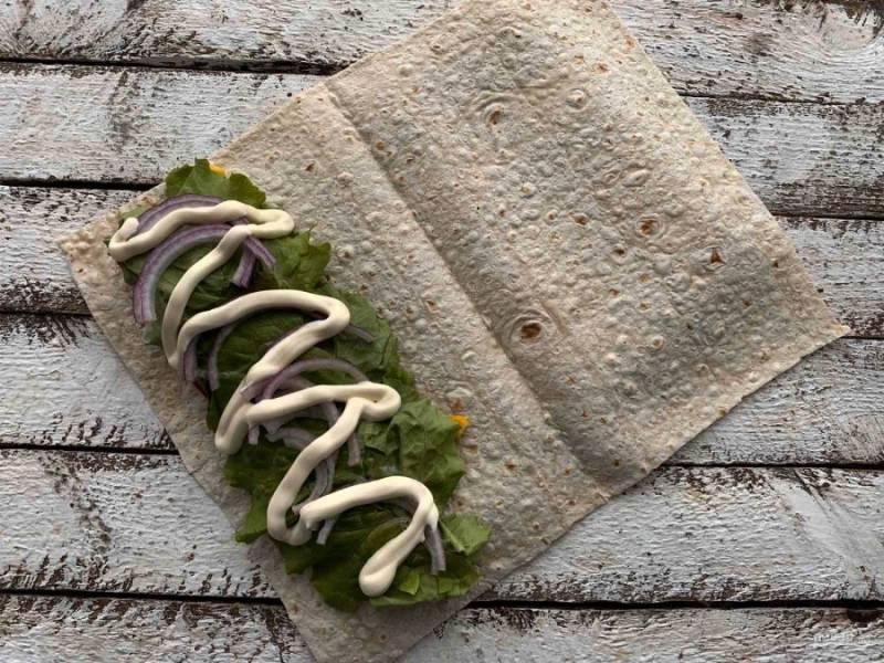 Сверху выложите лисья салата, нарезанный полукольцами красный лук и майонез.