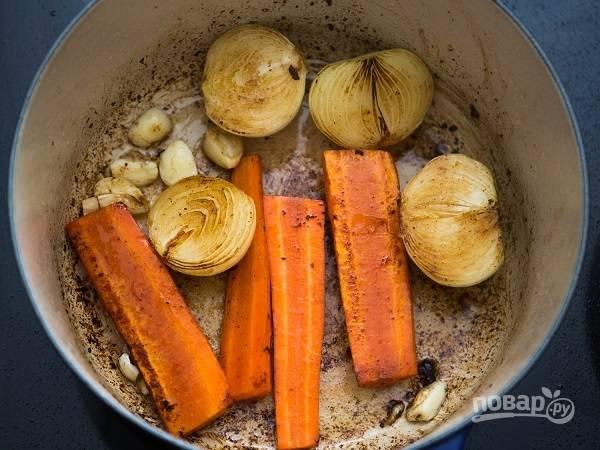 3. В сотейник добавьте немного масла и выложите пару луковиц и морковок, нарезанных пополам, а также чеснок. Обжарьте минут 5 на среднем огне.