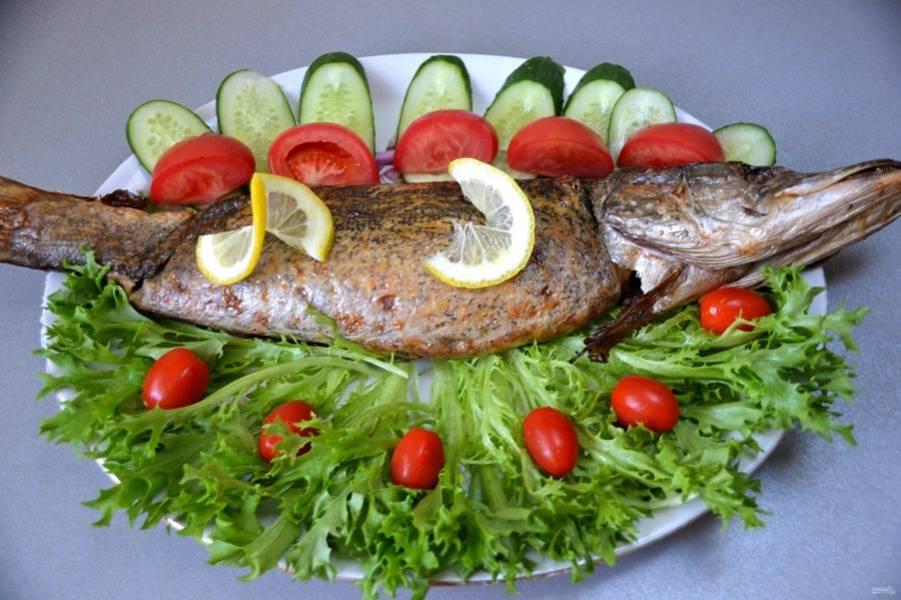 Дайте испеченной рыбе остыть до комнатной температуры, сервируйте для подачи свежими овощами и зеленью. Не забудьте удалить нитку, если зашивали брюшко.
