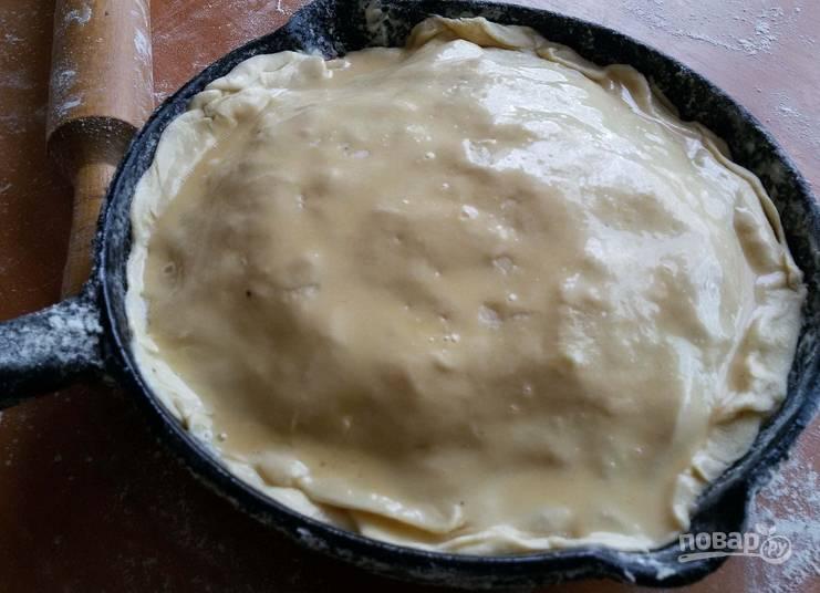 Накройте пирог оставшимся раскатанным тестом. Края защипните. Смажьте тесто сливочным маслом.