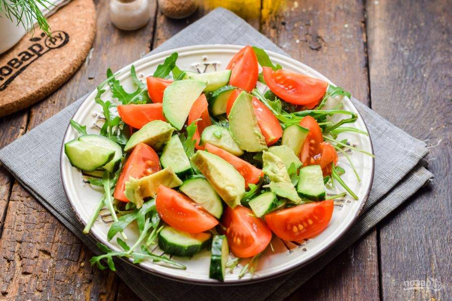 Очистите авокадо, нарежьте небольшими кусочками и переложите в салат.
