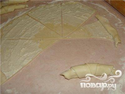 4.Тонким пластом раскатываем тесто, его поверхность смазываем начинкой, на восемь секторов разрезаем тесто. К вершине от основания закручиваем, загибаем как полумесяц.