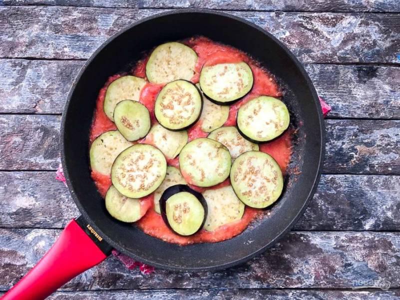 В сковороду вылейте измельченные помидоры и прокипятите их 4-5 минут. В помидоры выложите нарезанные кружочками баклажаны.