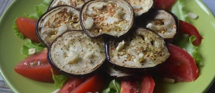 2. Помидор режем дольками. Выкладываем на тарелку листья салата и помидоры, сверху - чуть остывшие баклажаны. Измельчим чеснок и посыпаем блюдо сверху.