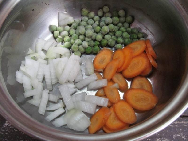 Нарезать мелким кубиком лук, морковь -ломтиками и выложить в кастрюлю с горошком, влить пару ложек оливкового масла, перемешать и жарить на среднем огне 3 минуты.