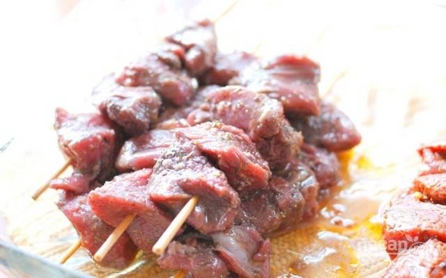 За полчаса до приготовления выставьте мясо в маринаде на стол при комнатной температуре. Если используете деревянные палочки для шашлыков, то замочите их в воде на 30 минут.