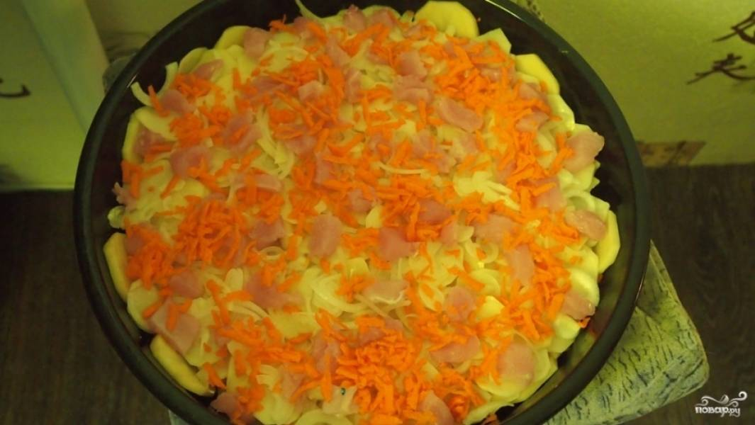 Слегка смажьте форму для выпекания маслом. Выложите первым слоем картошку, потом мясо. Затем снова картошку. Потом индейку, тертую морковку и лук, порезанный кольцами.