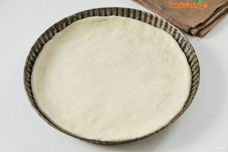 Подошедшее тесто раскатайте по размеру формы, аккуратно перенесите и сделайте небольшие бортики. Накройте чистым полотенцем и оставьте еще примерно на 20 минут.