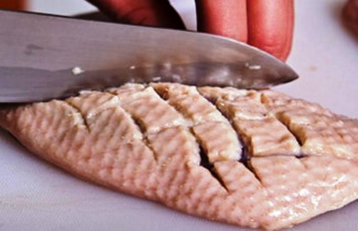 На коже сделайте надрезы в виде сеточки, это позволит мясу лучше прожариться и обжарьте кусочки мяса на сковороде до румянца.