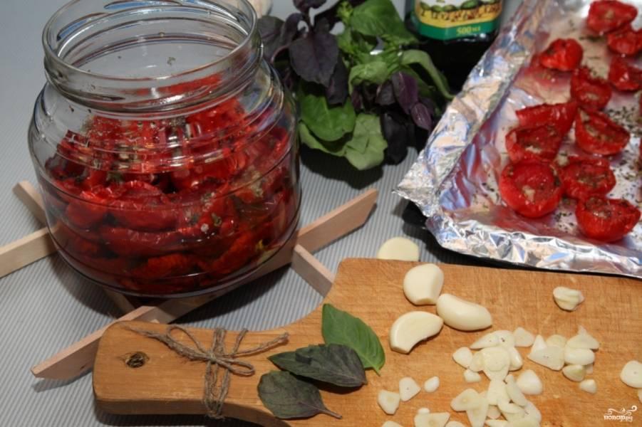 Готовые вяленые помидоры рекомендую сложить в чистую (можете простерилизовать) банку. Перекладывайте помидоры чесноком, порезанным на тонкие пластинки. А также добавляйте свежие листья базилика.
